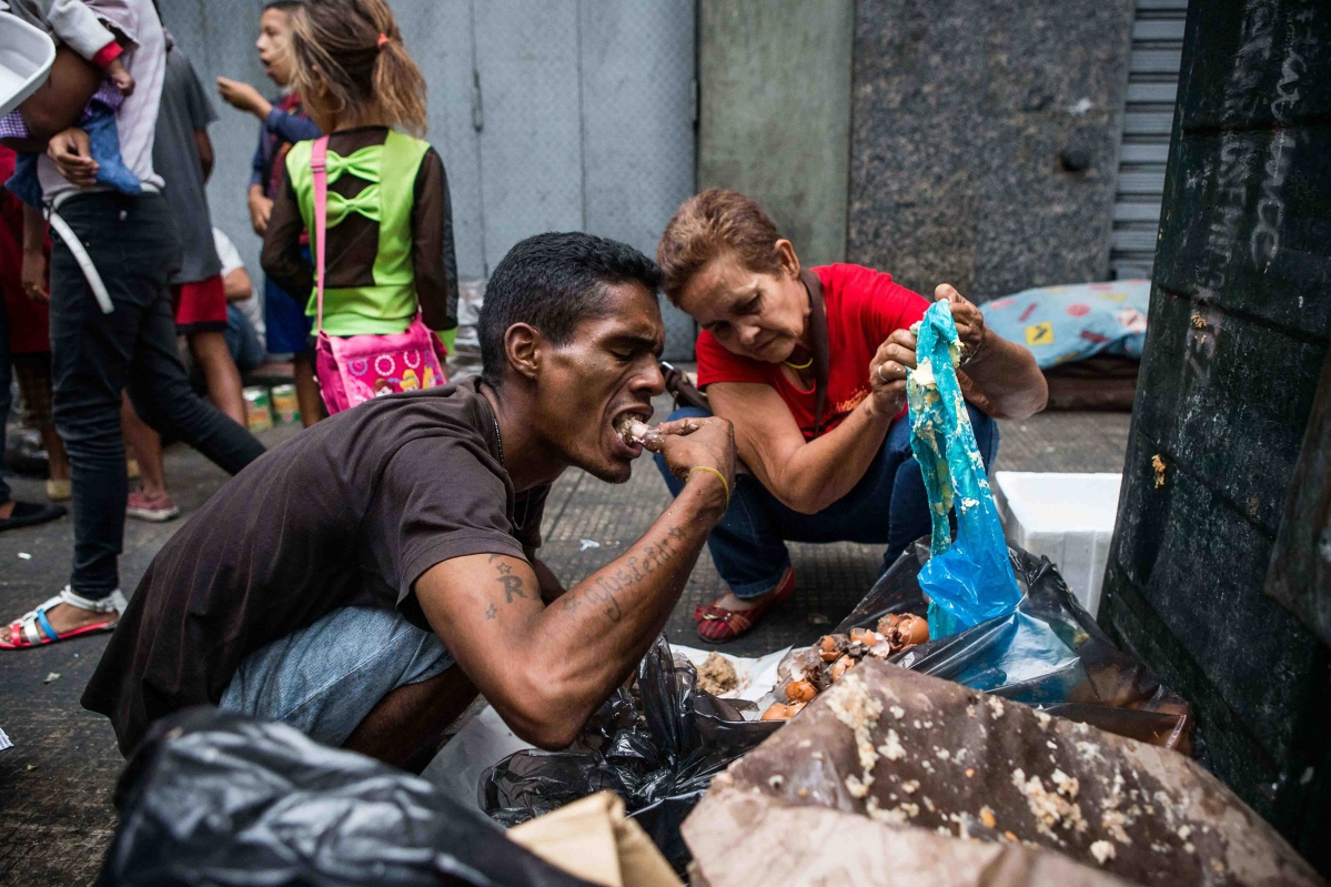 A man eats bits of food found in trash in Caracas in September 2016. Cristian Hernández—Climax