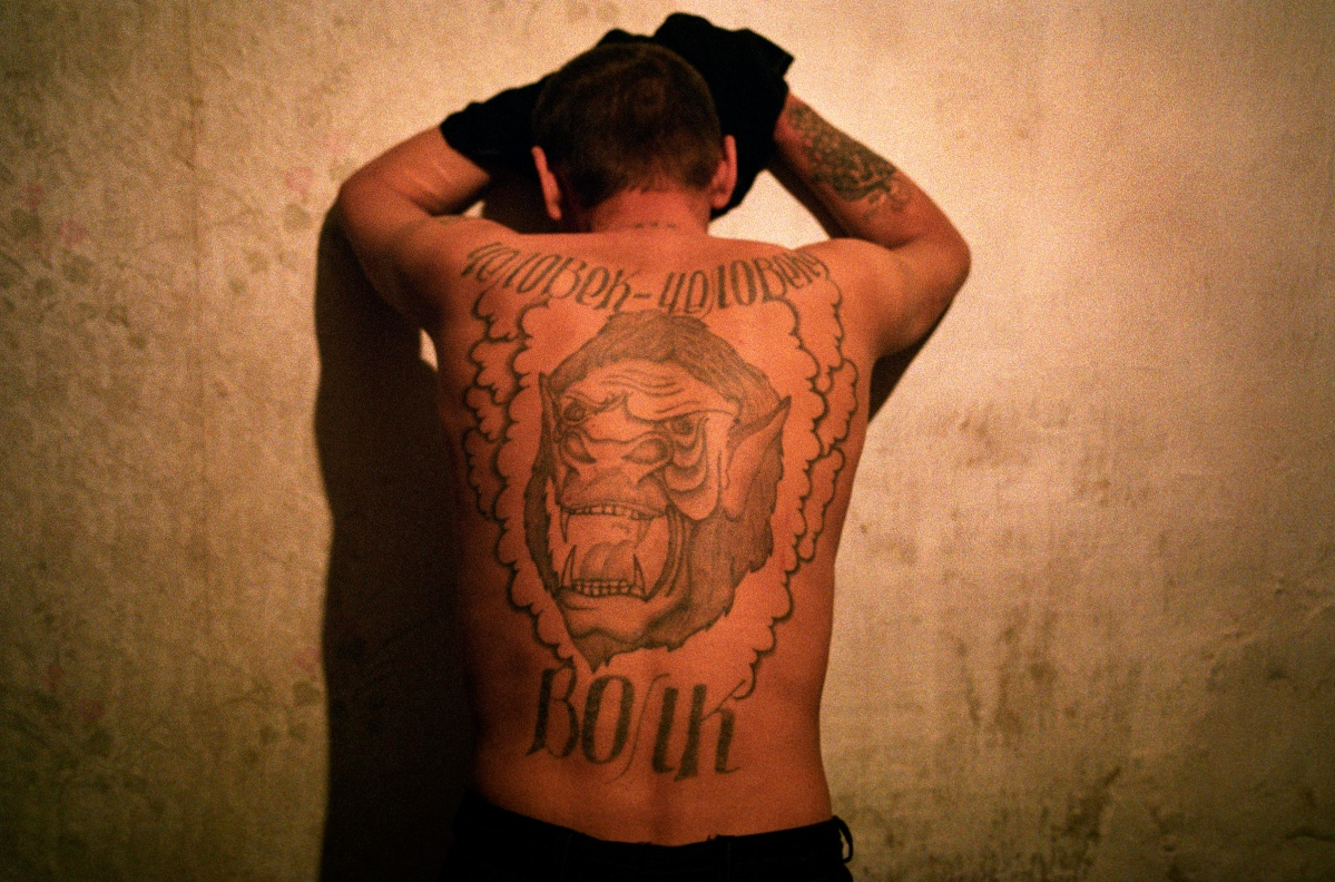 "Putin's Russia - The Darkness of Russia 2002 Rybachi village near Vladivostok. Volydya or ""Wolf"" lives in Rybachi village. The Russian tatoo on his back reads ""One man is a wolf to another man."" Just after he finished school he went to prison for stealing and was in possesion of a gun and received 2 and a half years. He says he had to steal because his family didn't make enough money. After he got out of prison he wanted to join the army. He longed for a normal life and he knew that without the army he had not chance to stay out of jail. The army commission rejected him with the following explanation ""We won't give you a gun so you can rob someone else."" He could not find a job and was returned to prison for stealing again. When he got out of prison a local policeman told him ""Let us know when you decide to go back to jail, we'll come and drive you there."" Stanley Greene—NOOR"