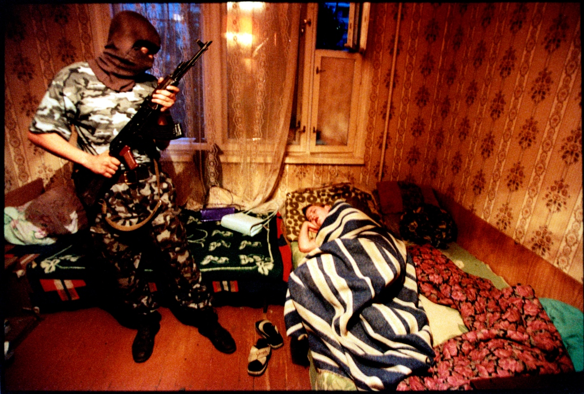 Putin's Russia - The Darkness of Russia June 2001 Volgograd, Russia Drug raid, the OMON squad is a special purpose police unit, militia-comando outfit. They wear military style uniforms and sometimes masks, blue flak jackets and carry machine pistols, AK-47's. Stanley Greene—NOOR