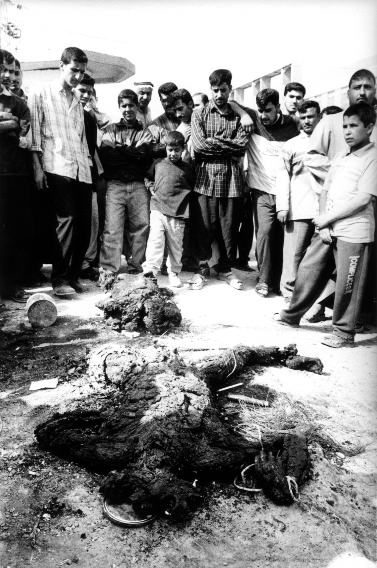 FALLUJAH, IRAQ - MARCH 31: An Iraqi mob gather around a mutilated corpse following an attack on two civilian vehicles on March 31, 2004 in Fallujah, Iraq. Local residents vented their anger by throwing stones at the burning vehicles and dragged out the mutilated bodies. The incident followed an other attack in the town earlier in the day on a U.S. military convoy that killed 5 American soldiers. PHOTOGRAPH BY STANLEY GREENE--AGENCE VU. Stanley Greene—Agence Vu