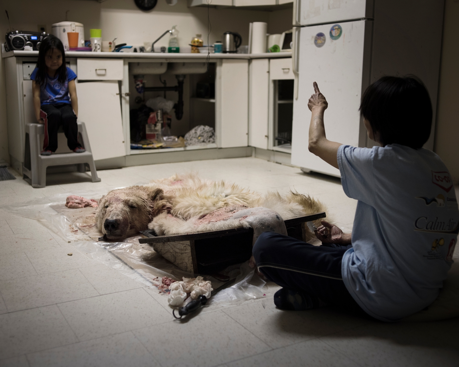 A girl watching her grandmother removing the fat from a polar bear pelt. More than half of the Inuit diet consists of fresh game.