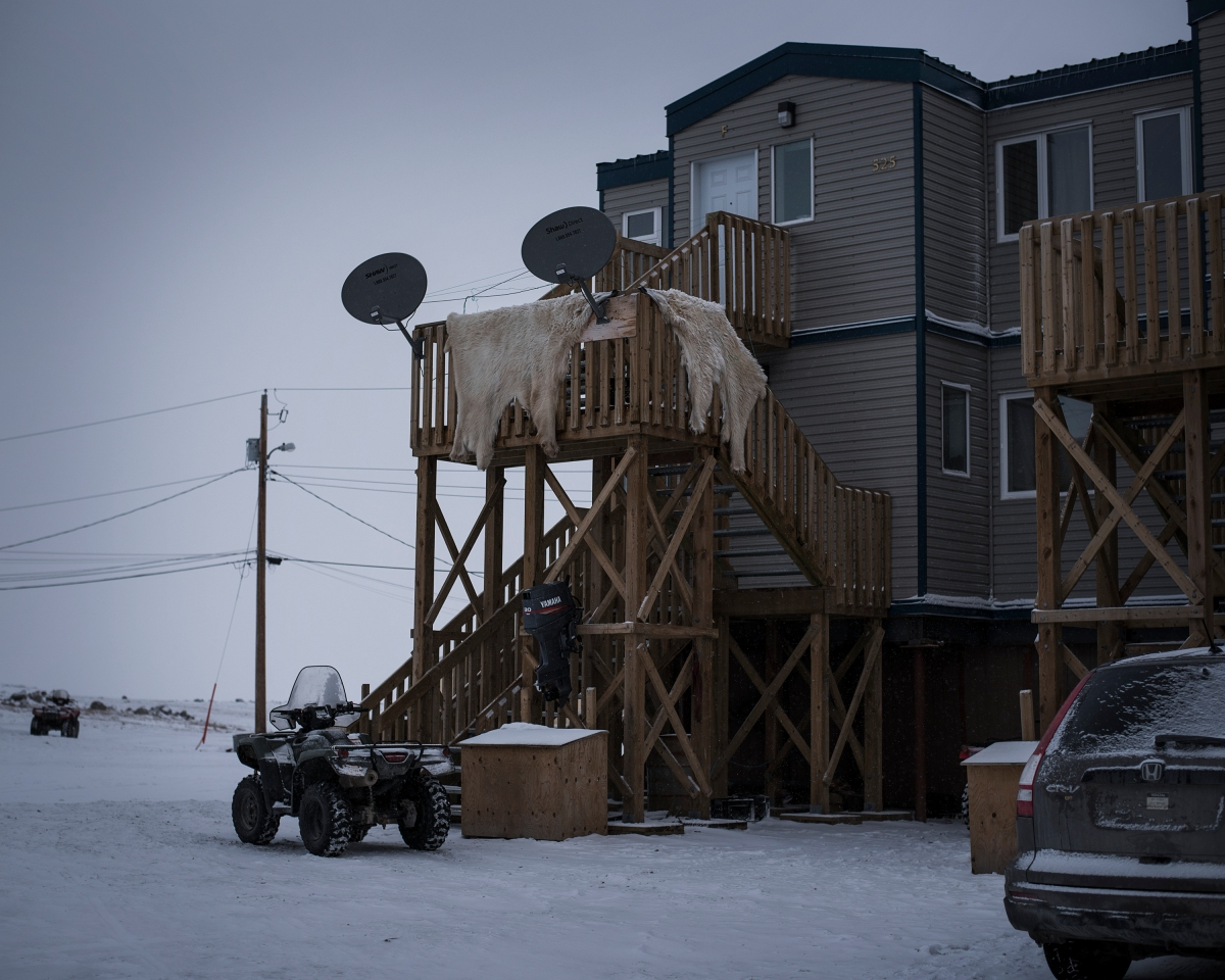 Polar bear pelts hang outside to dry. In the 1960s the Canadian government encouraged the traditionally nomadic Inuit to move into subsidized housing.