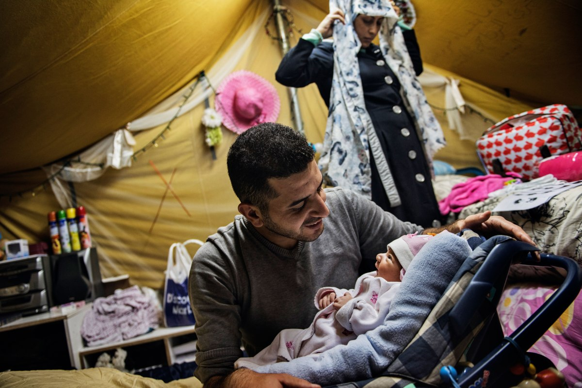 Inside their tent in the Oreokastro camp, the 22-year-old new mother stands behind her husband Yousef and their newborn daughter Rahaf. Lynsey Addario—Verbatim for TIME