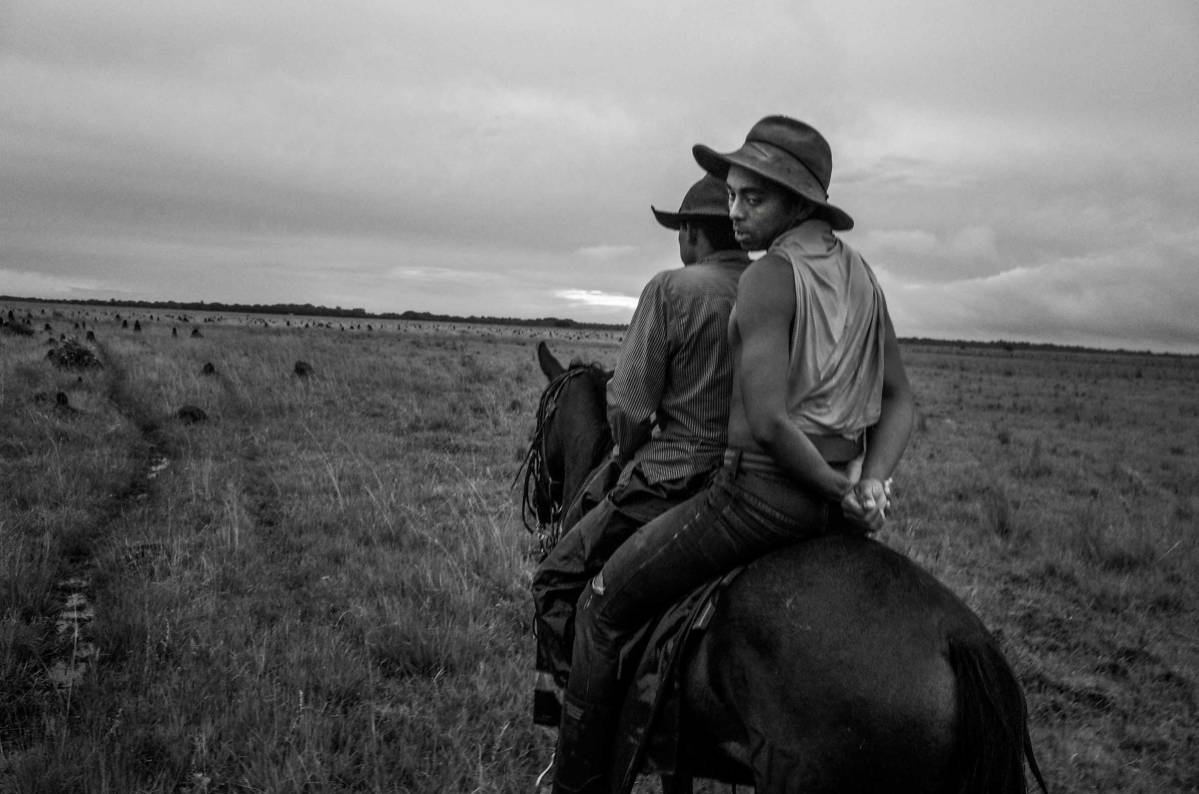 A Llanero shares a companion's horse after his own horse grew overtired during the Trabajos del Llano. Santana Ranch Savannahs , Casanare State, The Orinoco Plains, Colombia, 2015.