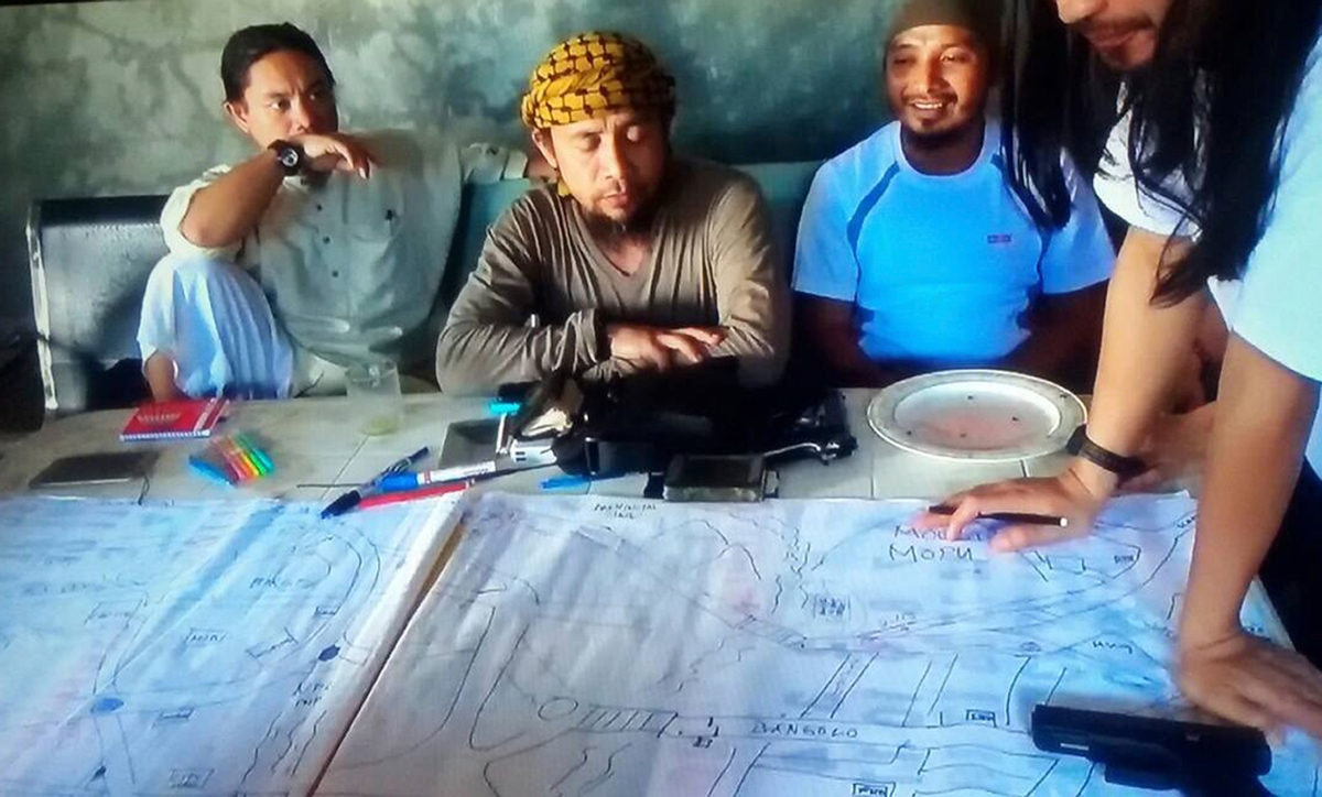 A screengrab from an undated video shows the purported leader of the Islamic State group Southeast Asia branch, Isnilon Hapilon, center, at a meeting of militants at an undisclosed location. AP