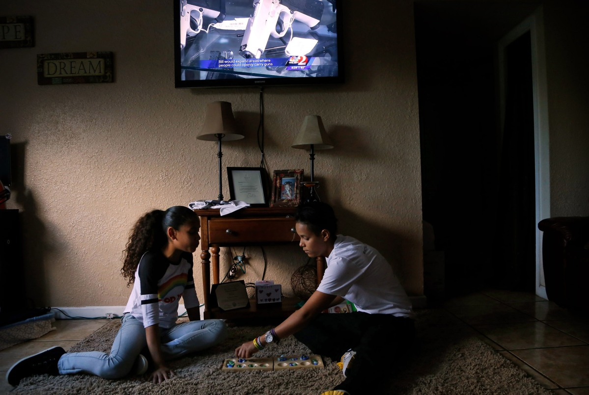 Kali (right) and her sister Kinnie, play a game at home on Monday, December 12, 2016. Behind them a news report airs on a bill to loosen restrictions where people can openly carry firearms.