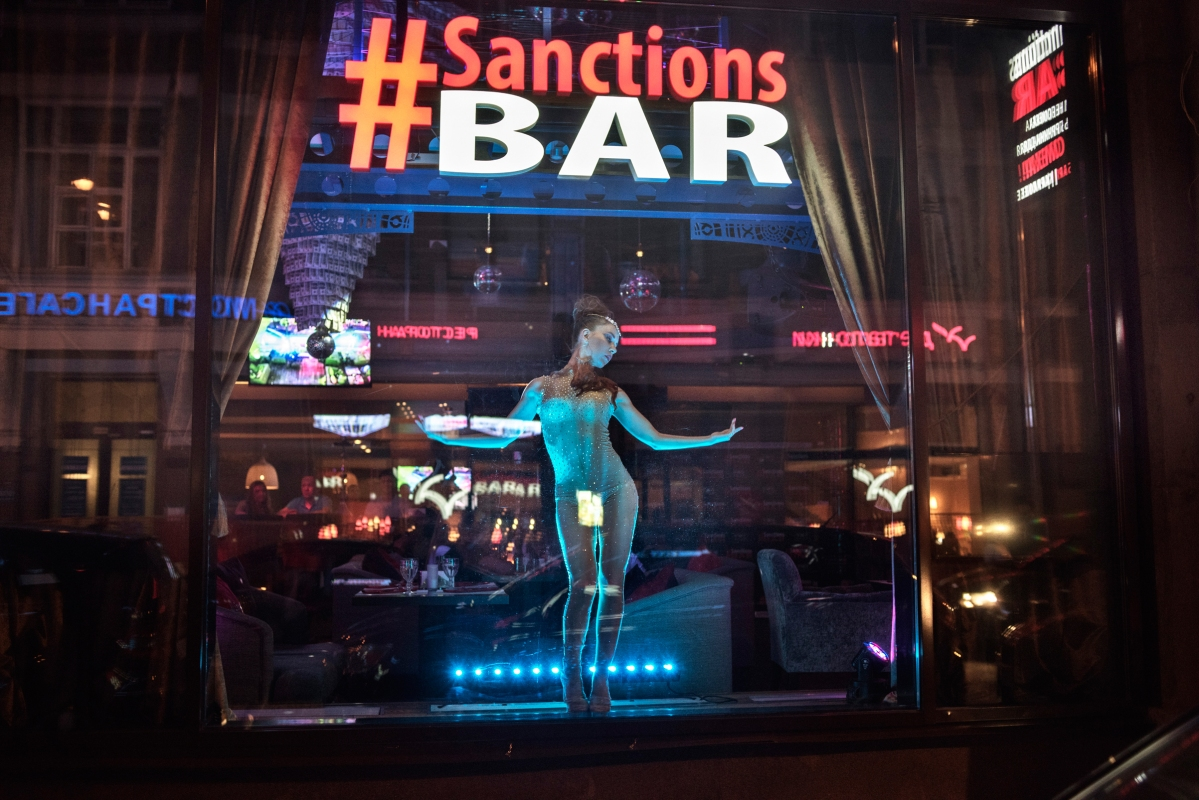 A dancer in the window of the #Sanctions Bar in Moscow, June 2015. Designed to make light of the economic sanctions that the U.S. and its allies imposed on Russia over the conflict in Ukraine, the bar features oil drums, a chandelier draped in fake $100 bills, and a menu poking fun of then-President Barack Obama.
