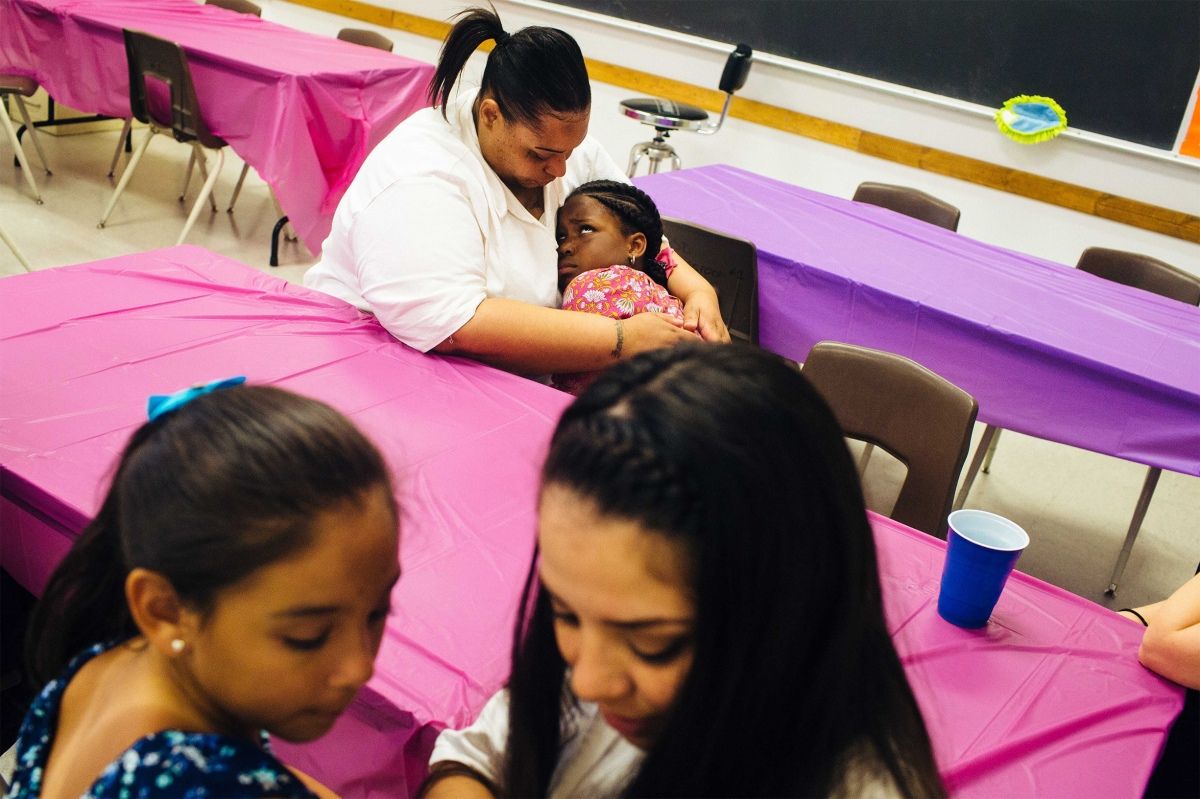 Trunarah Miller, 8, cuddles with her mother, Lakeshia Kennedy as Layla Arenas, 7, shares secrets with her mother Magan Garcia. Sara Naomi Lewkowicz for TIME