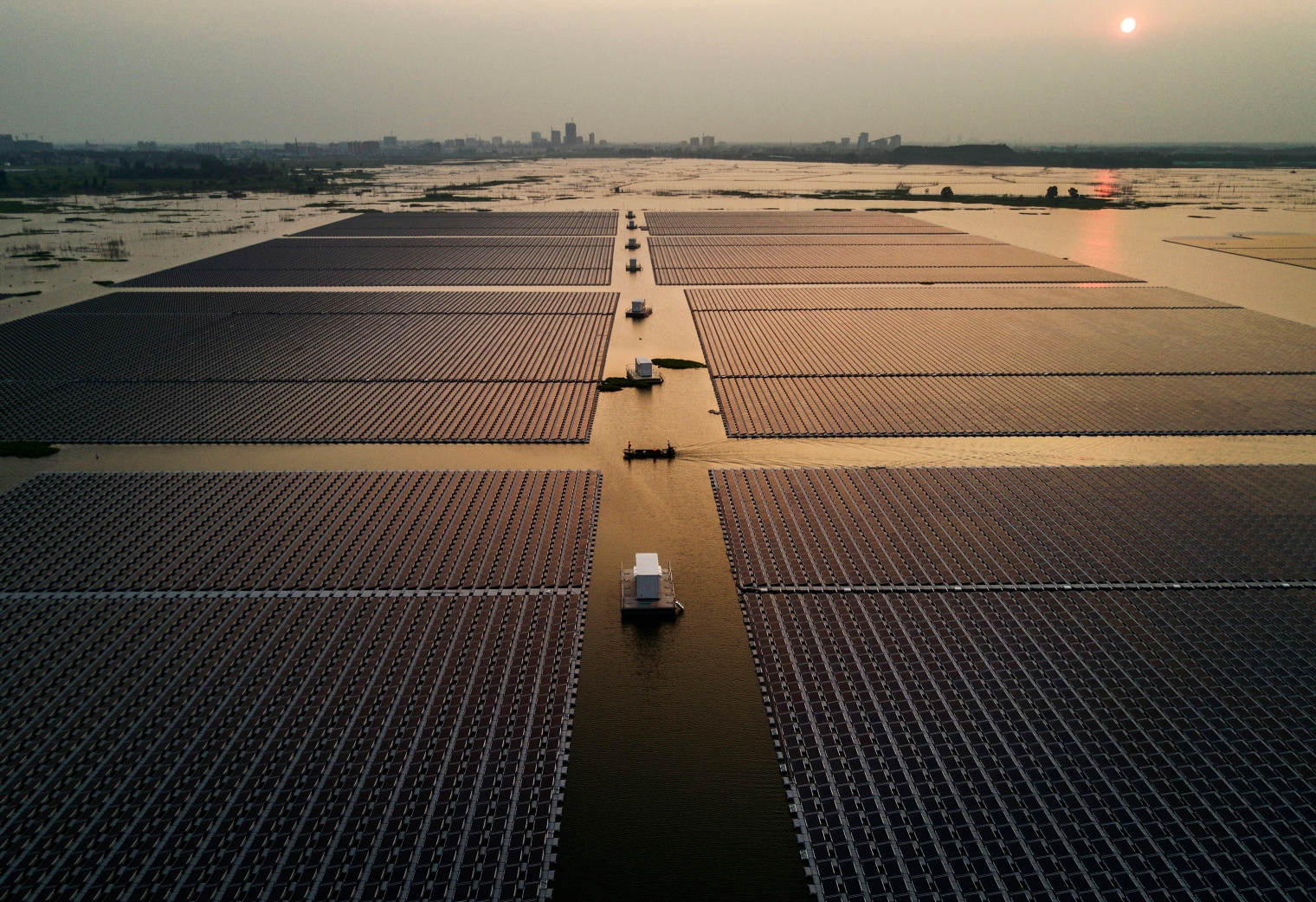 Workers ride in a boat through a large floating solar farm project.