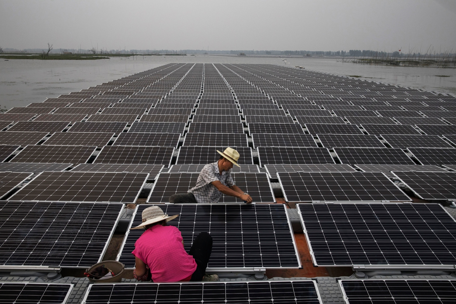 Workers prepare panels that will be part of a large floating solar farm project.