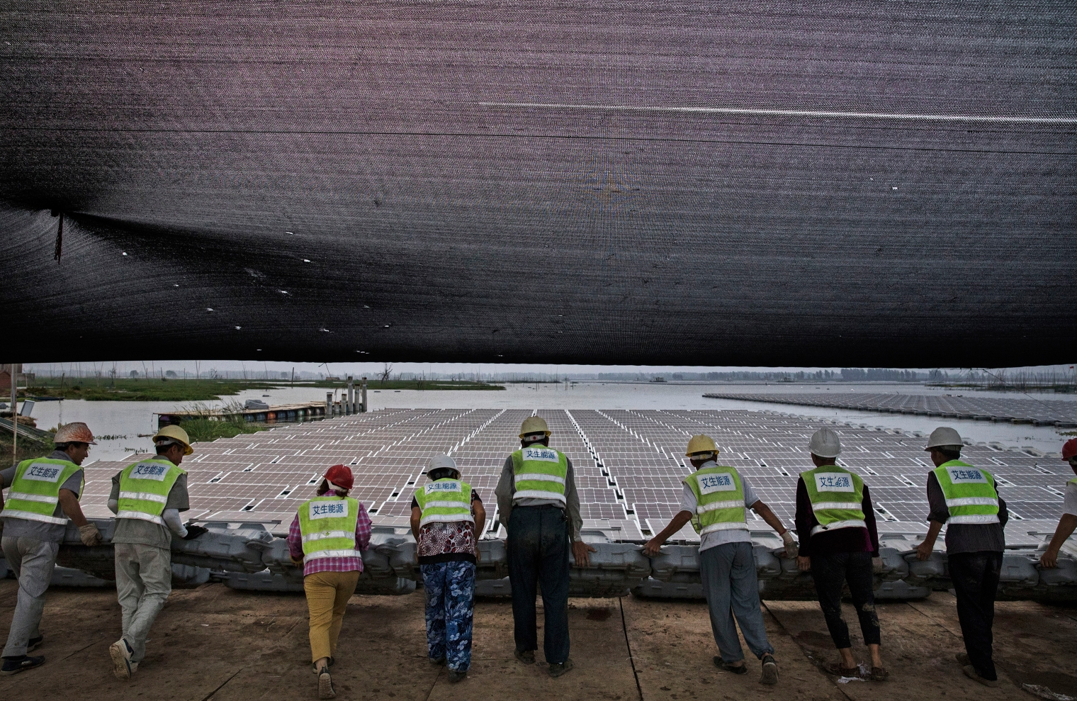 Chinese workers push a section of panels into the water.