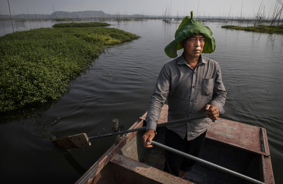 Chinese fisherman Wang Duoli, 50, whose family home was flooded out more than a decade ago, paddles in his boat near the site of a large floating solar farm.