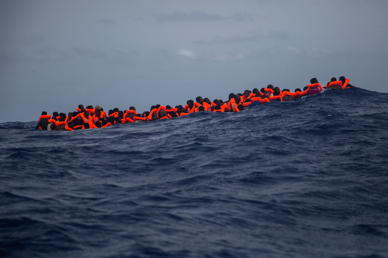 Sub-Saharan migrants who received life jackets wait to be transferred from the rubber boat to the Open Arms vessel of the Spanish NGO.