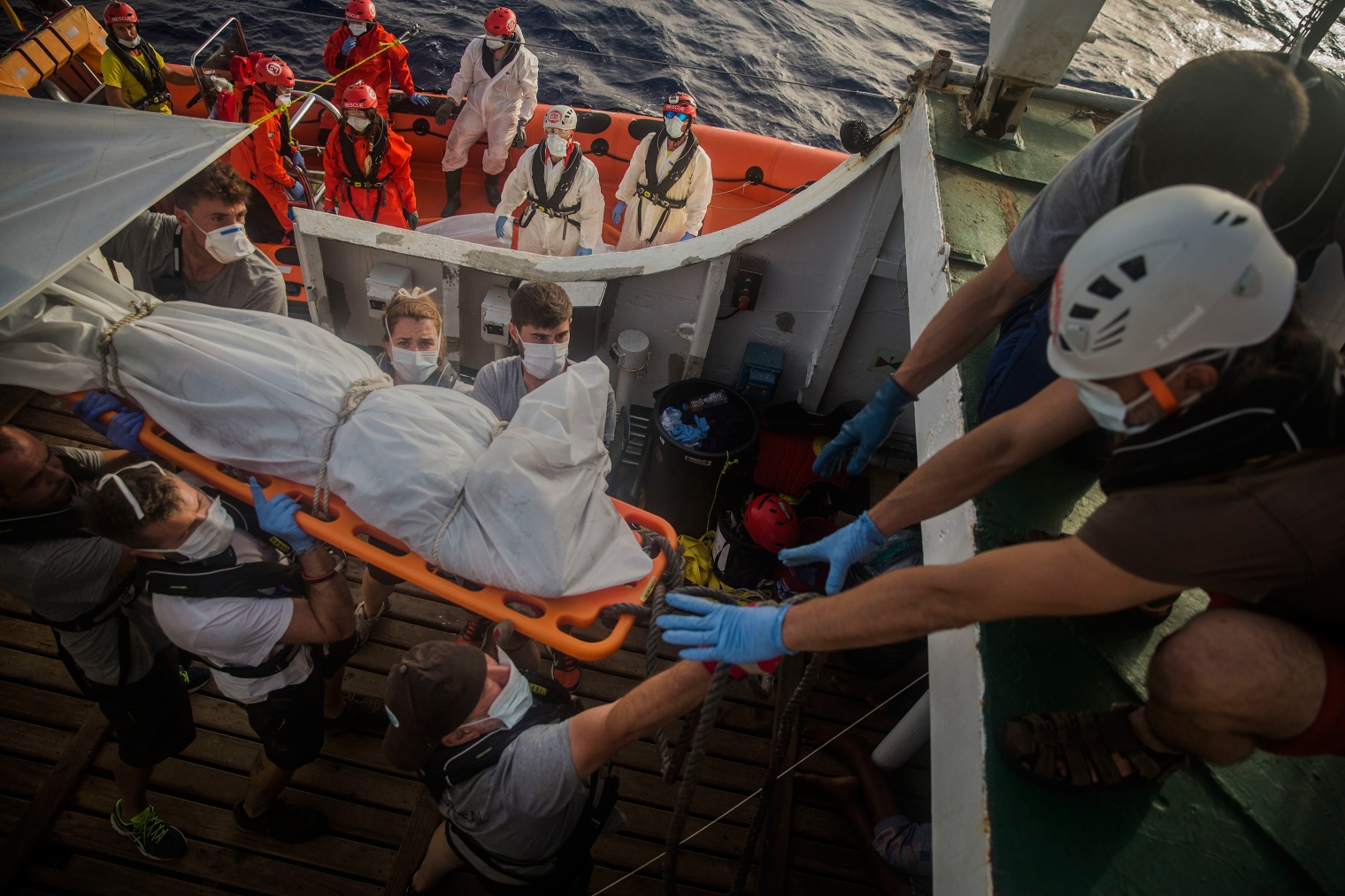 The body of a dead migrant is transferred from the rubber boat to the Open Arms vessel.
