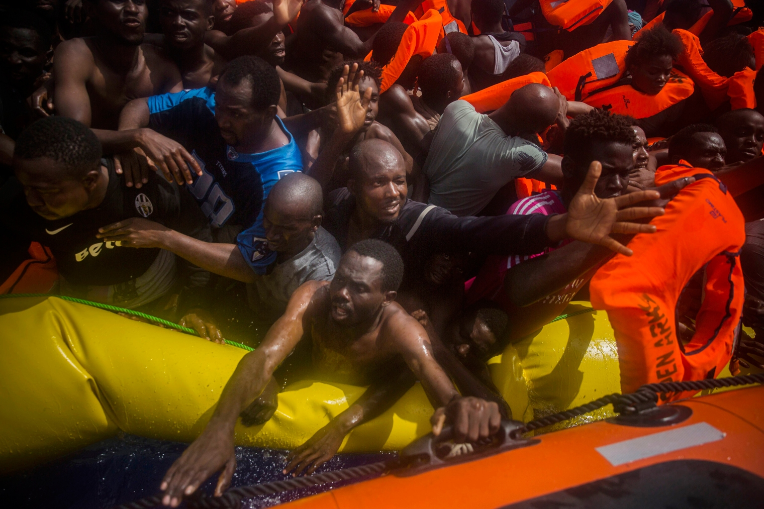 Migrants receive life jackets during the rescue.