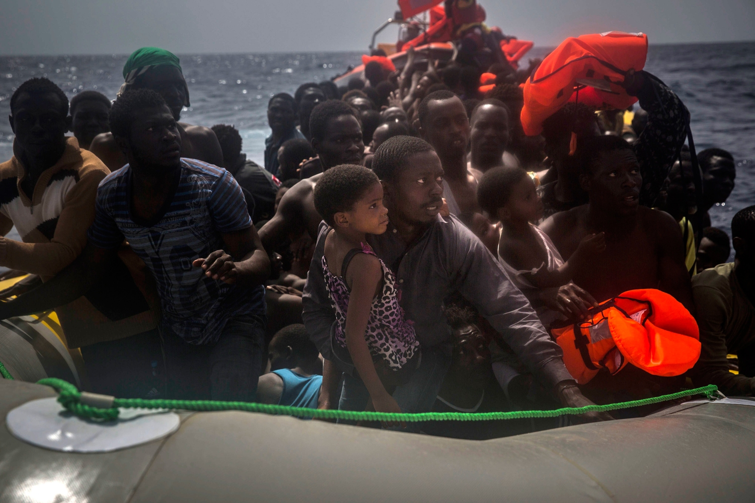 A man and young girl wait to receive life jackets.