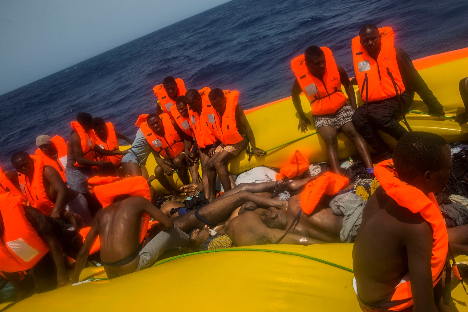 Migrants waiting to be rescued sit on the edge of the rubber boat, around a pile of bodies.