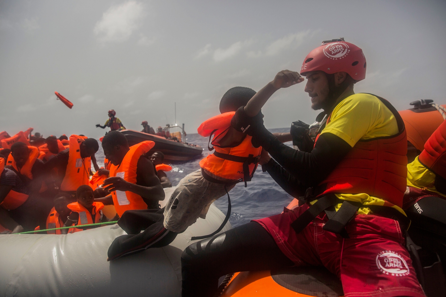 A child is helped by an aid worker during the rescue.