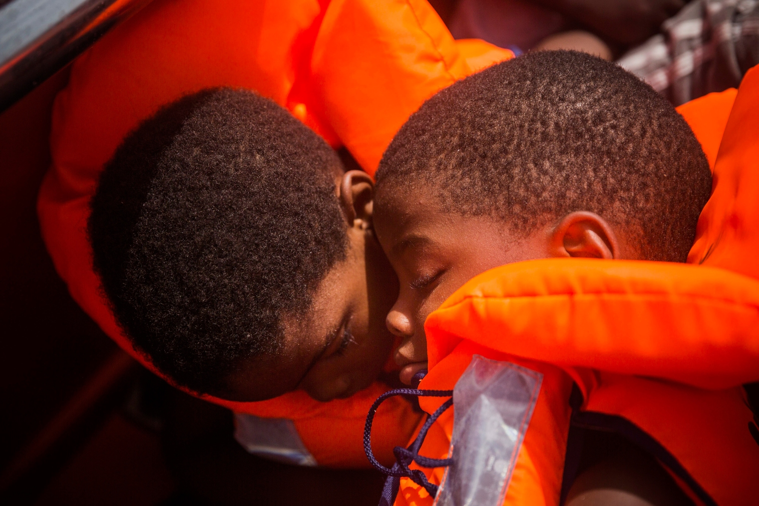 Two children sit in life jackets during their rescue.