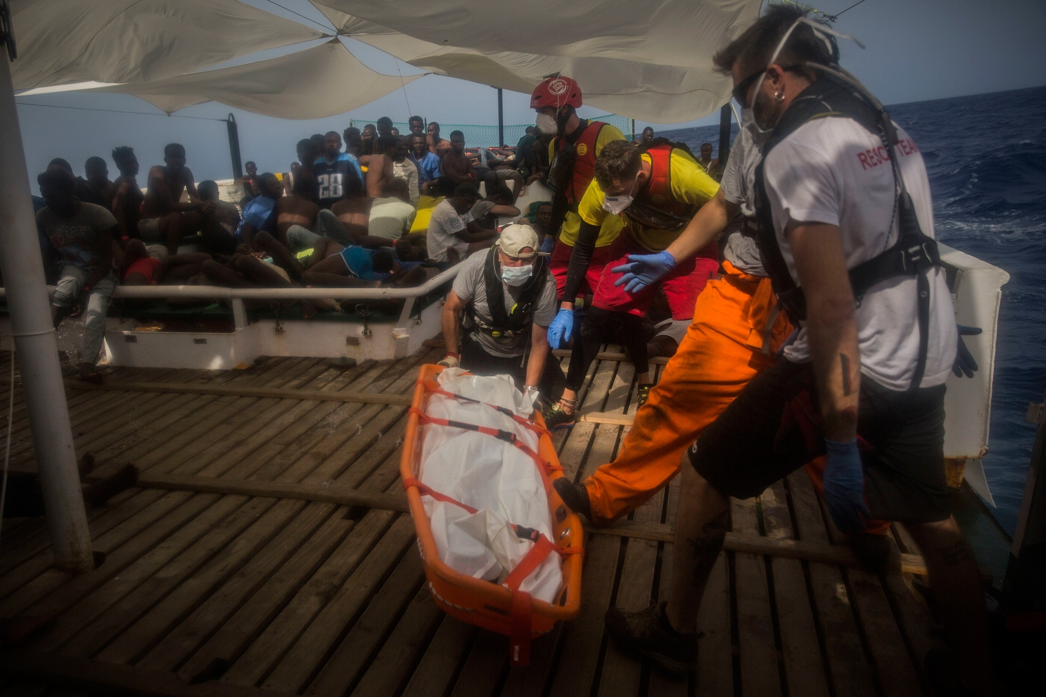 Aid workers recover dead bodies of migrants from inside het rubber boat.