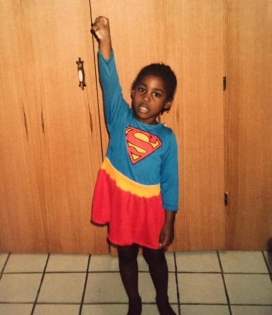 Issa Rae as a young girl posing in a Supergirl costume.