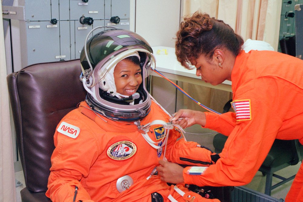 Mae Jemison waits as her suit technician performs a spacesuit check at the Operations and Checkout Building at Kennedy Space Center on launch day in September 1992.