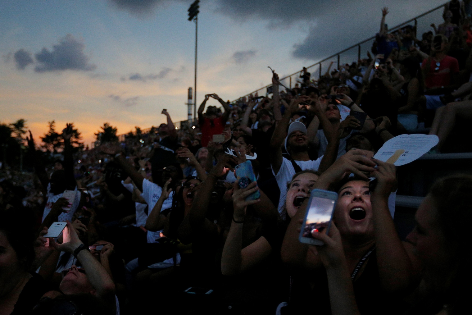 People react to the total eclipse in the football stadium at Southern Illinois University in Carbondale, Illinois, on Aug. 21, 2017.