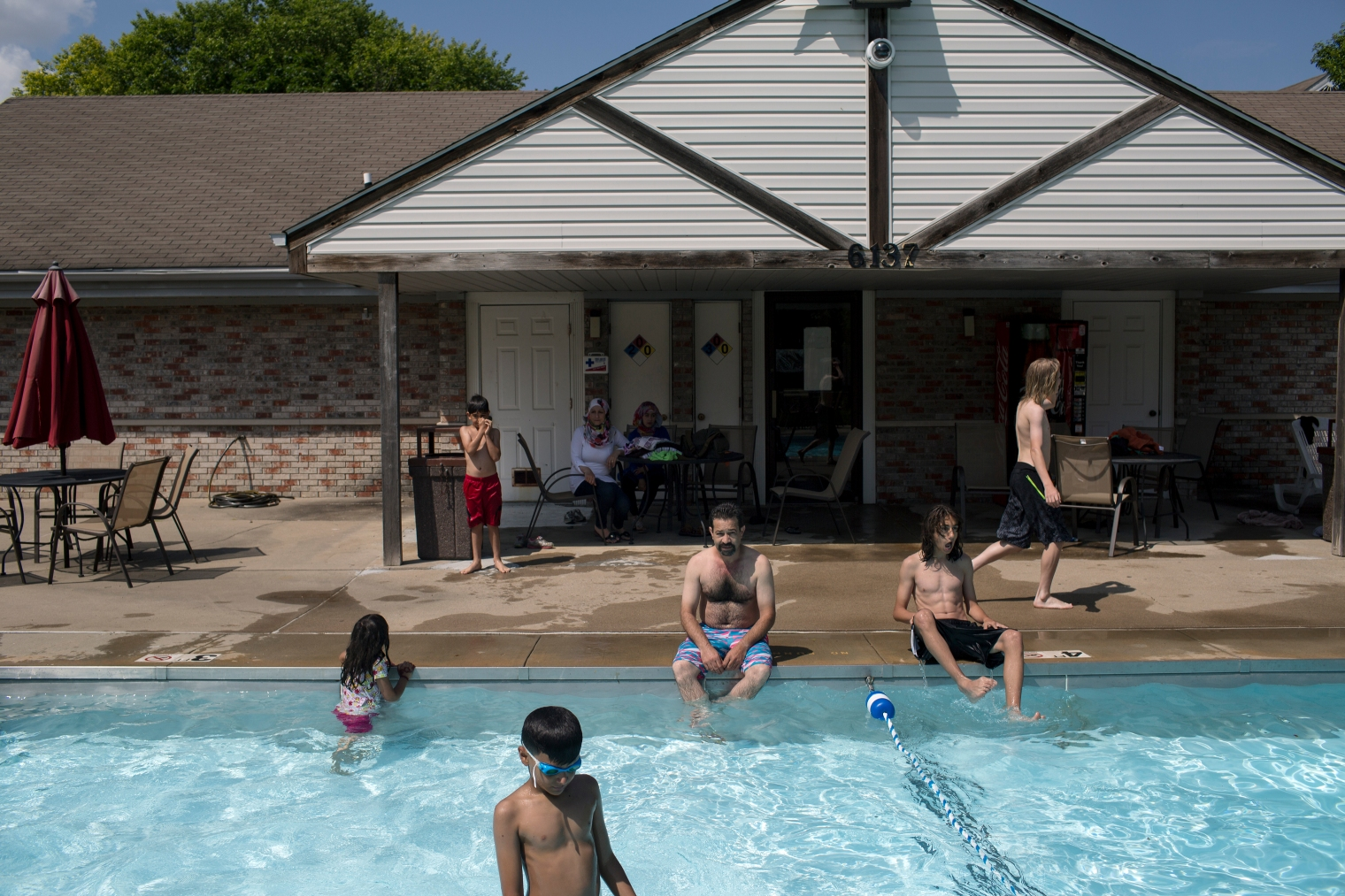 Abdul Fattah Tameem and his family enjoy the pool on a hot summer day at the family's new apartment complex in West Des Moines, a suburb of Des Moines, Iowa.