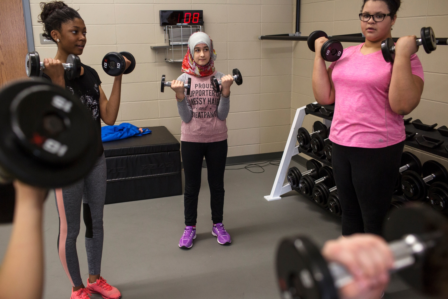 Sedra Tameem lifts weights during gym class at Waukee Middle School. Waukee is a suburb of Des Moines, Iowa.
