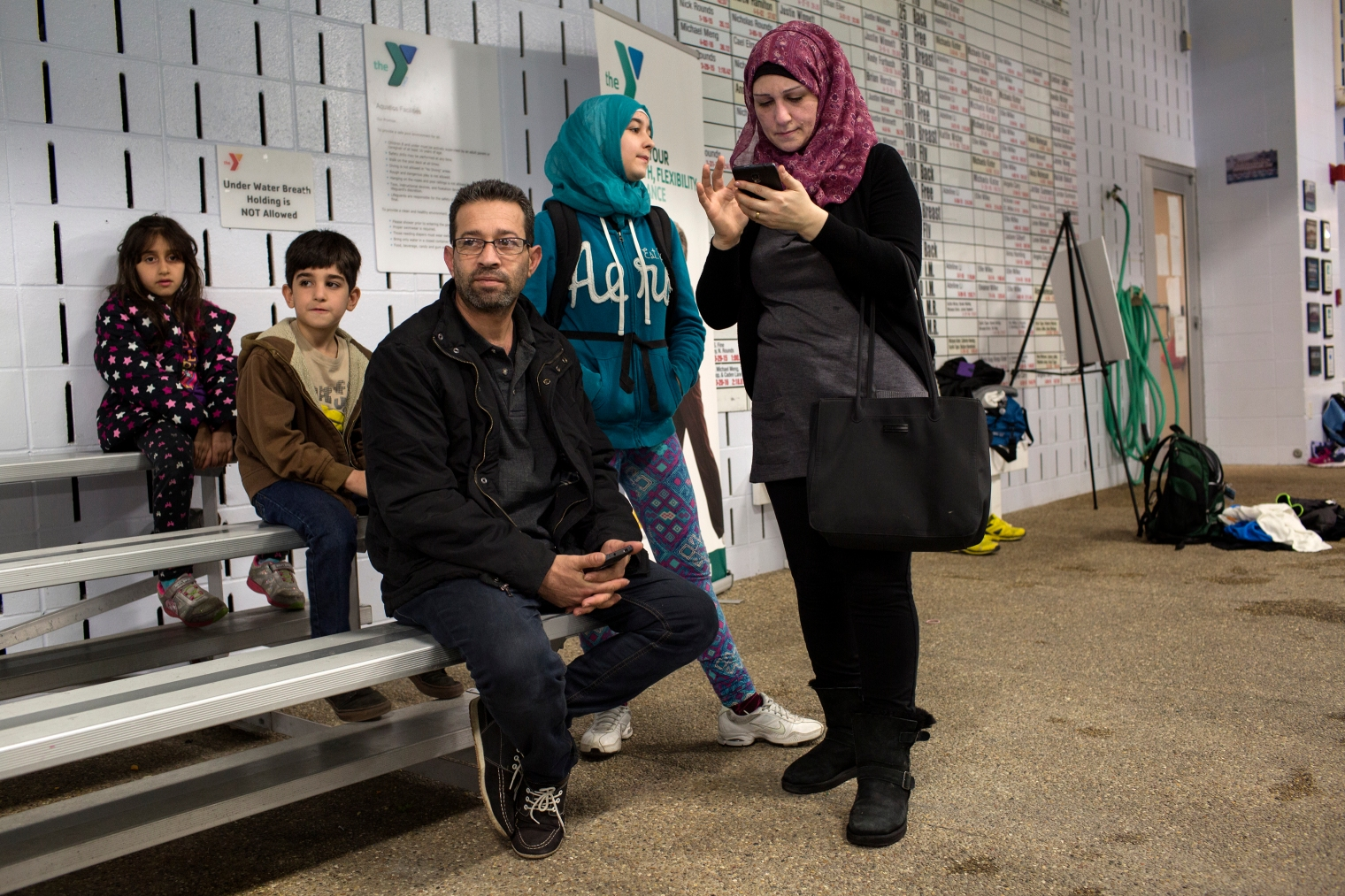 Abdul Fattah Tameem and his wife, Ghazweh Aljabooli, watch there two oldest sons, Nazeer and Haidar, swim at a local pool.