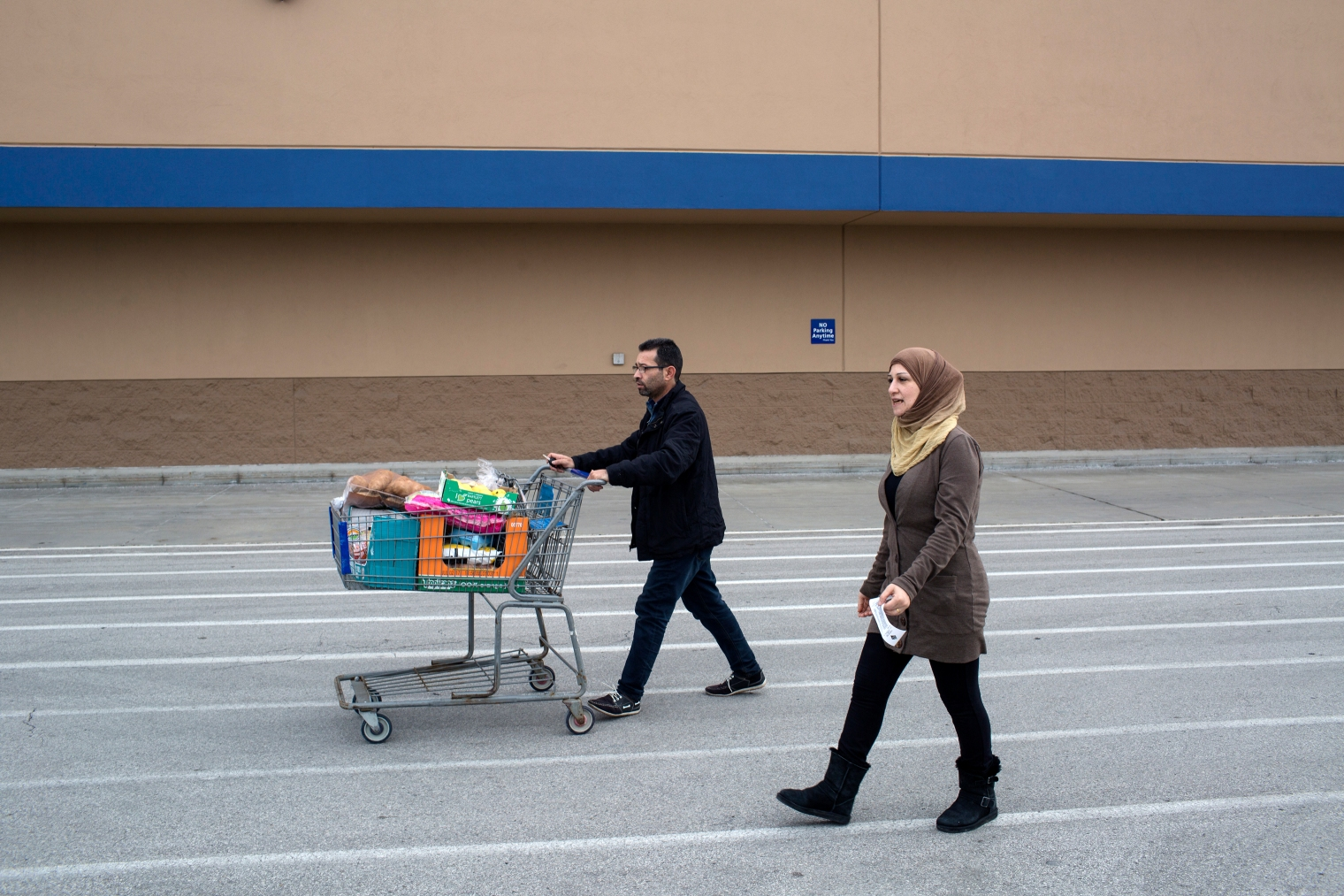 Abdul Fattah Tameem and his wife, Ghazweh Aljabooli, leave the store after shopping for their family. The parents of five moved their family to West Des Moines, a suburb of Des Moines, Iowa.