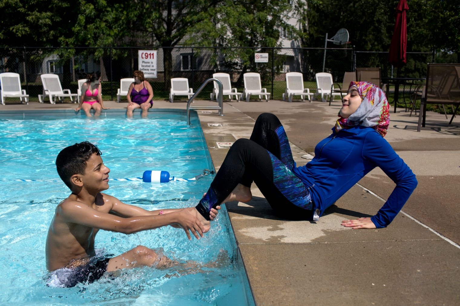 Sedra Tameem pulls away from Taha Albomo Hammed as he tries to pull Sedra into the pool at the Tameem's apartment complex in West Des Moines, Iowa.