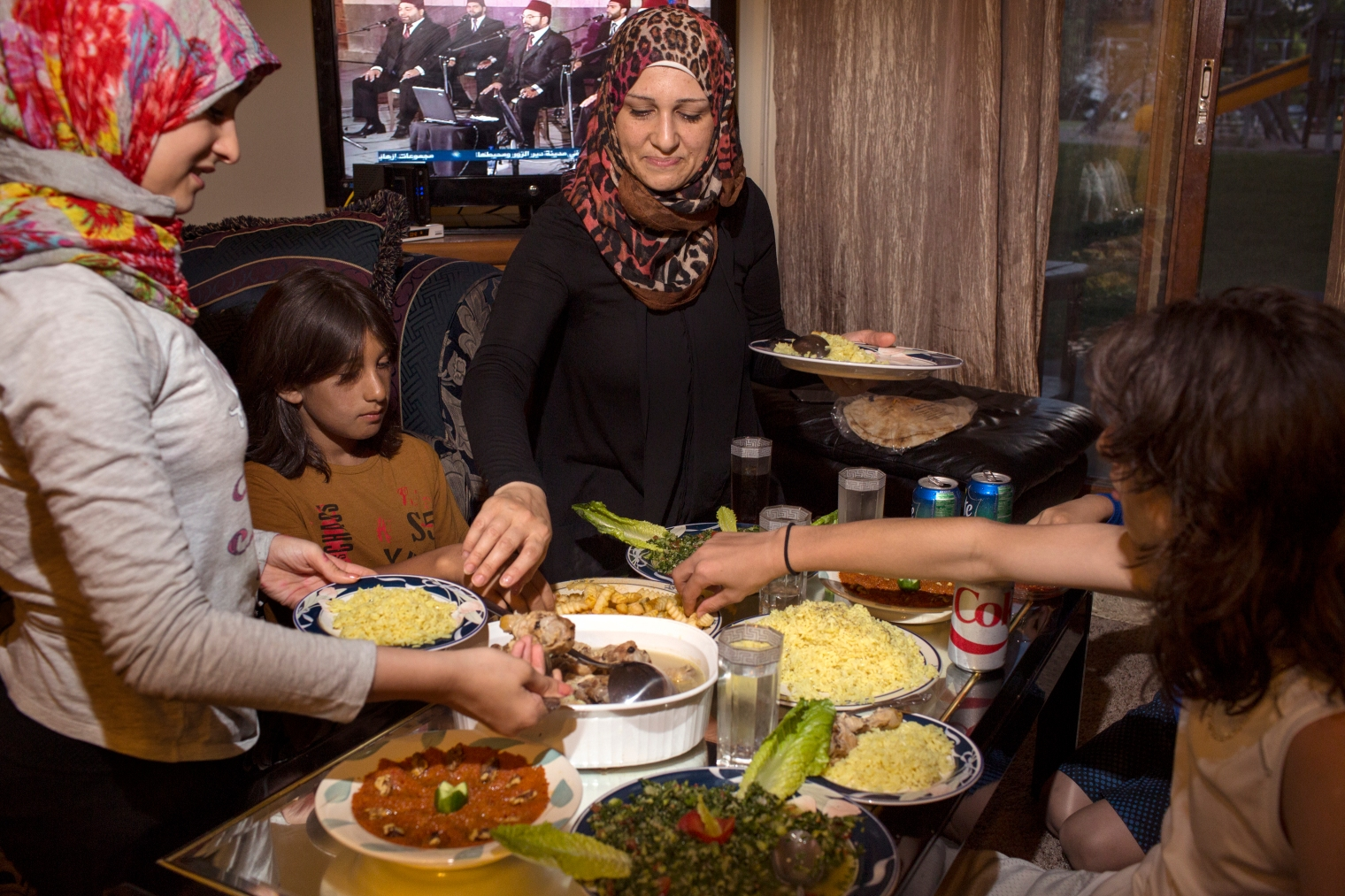 Ghazweh Aljabooli and her children eat together after breaking their fast during Ramadan at their apartment in West Des Moines, Iowa.