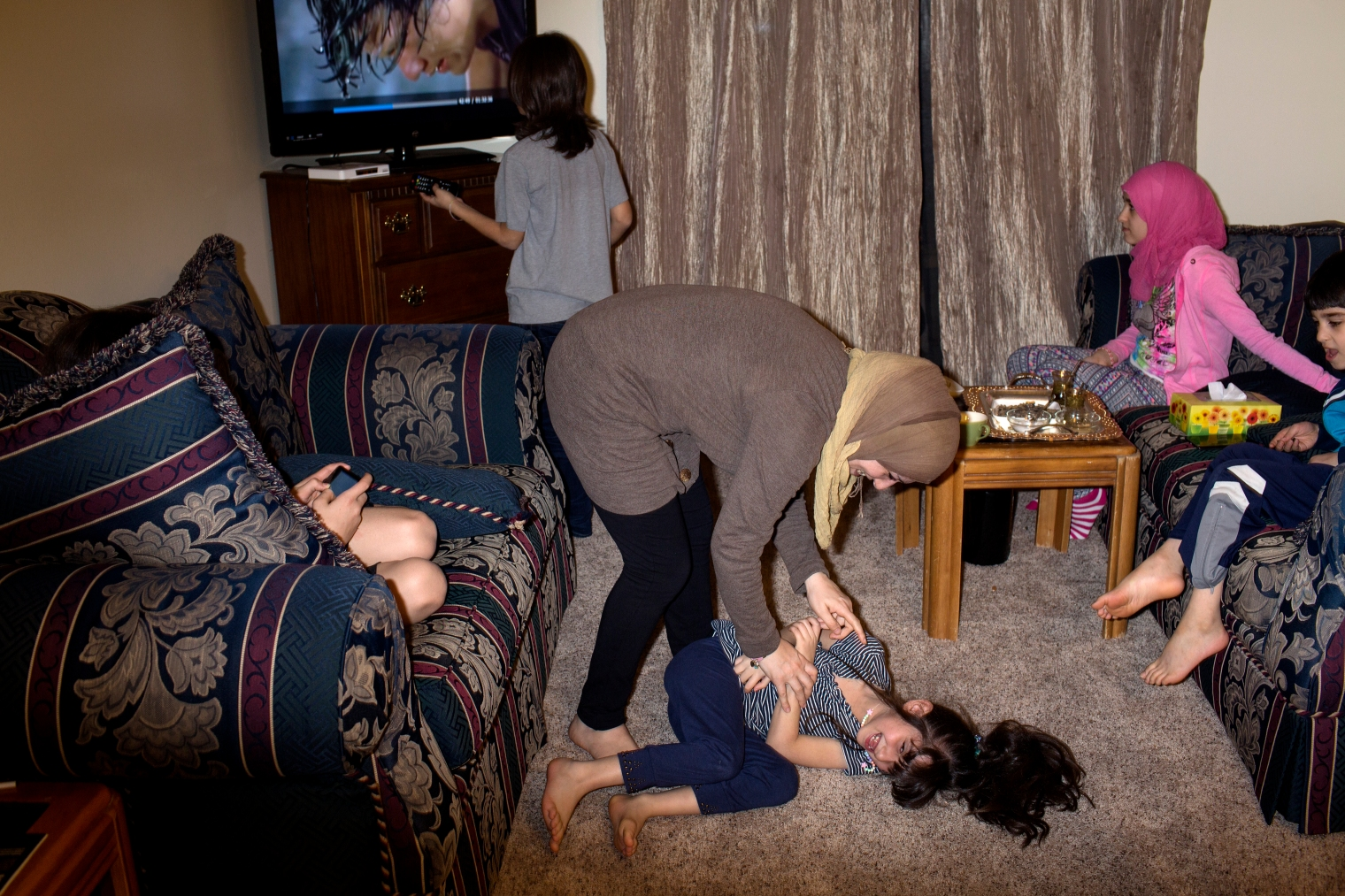 Ghazweh Aljabooli plays with her daughter Hala at the family's new apartment in West Des Moines, Iowa.