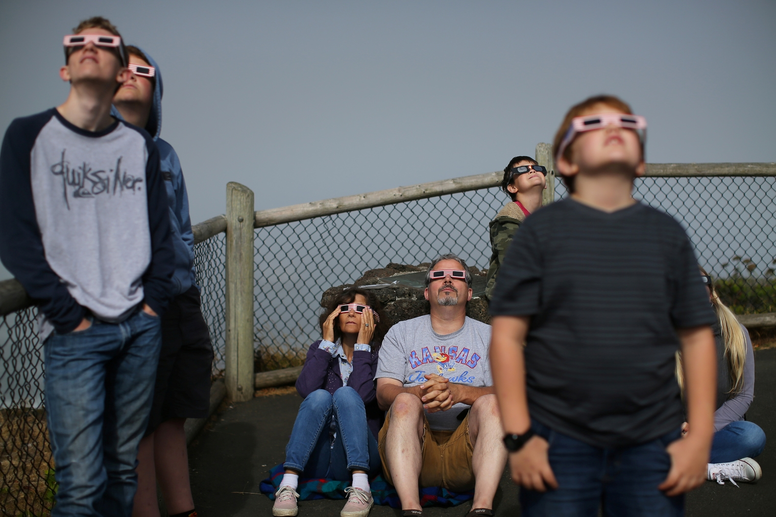 A boy uses solar viewing glasses as the sun emerges through fog cover before the solar eclipse in Depoe Bay, Oregon on Aug. 21, 2017.