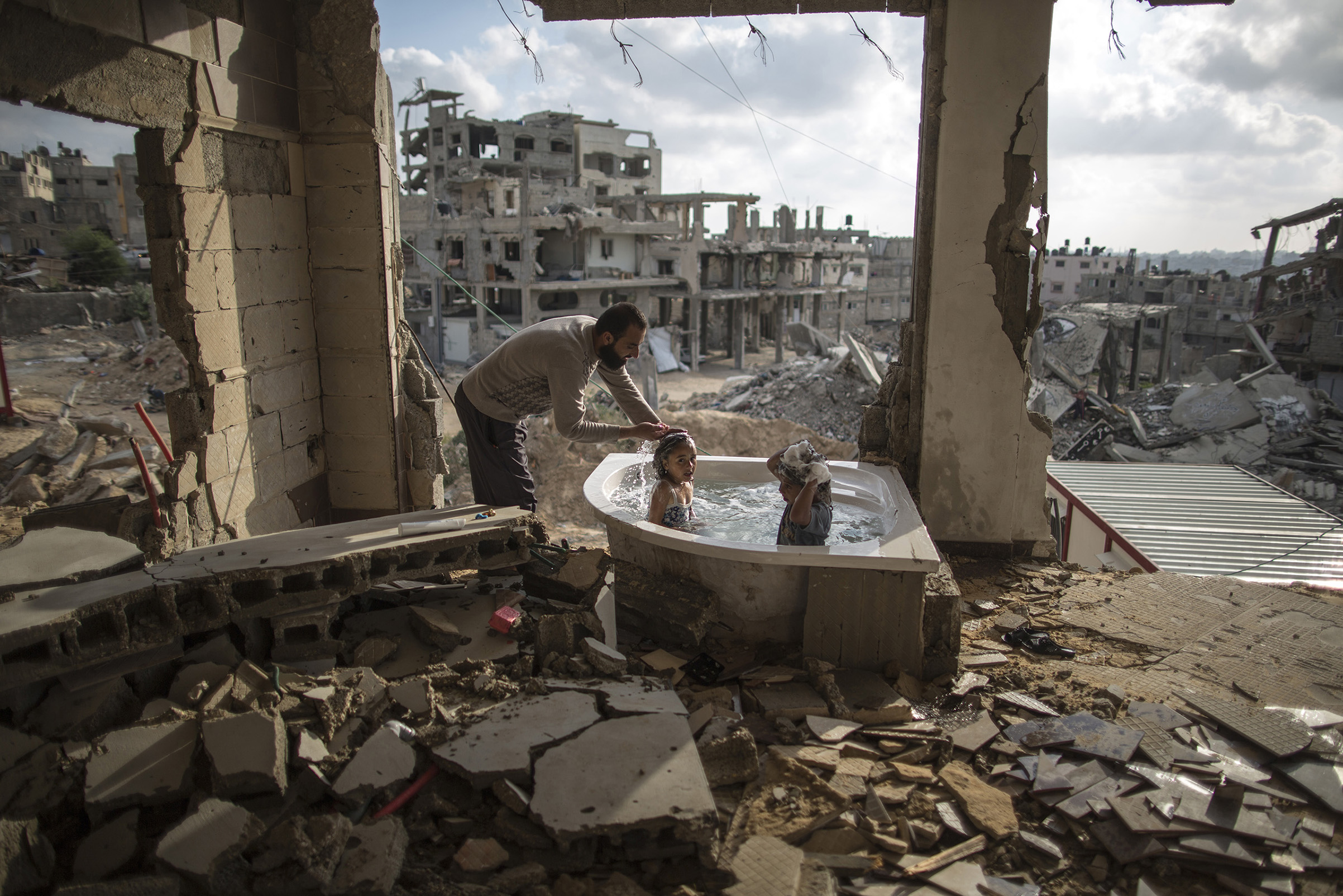 June 26, 2015  .Salem Saoody, 30, is getting his daughter Layan (L) and his niece Shaymaa 5 (R) in the only remaining piece from their damaged house, which is the bathing tub. They now live in a caravan near the rubbles. By Wissam Nassar.