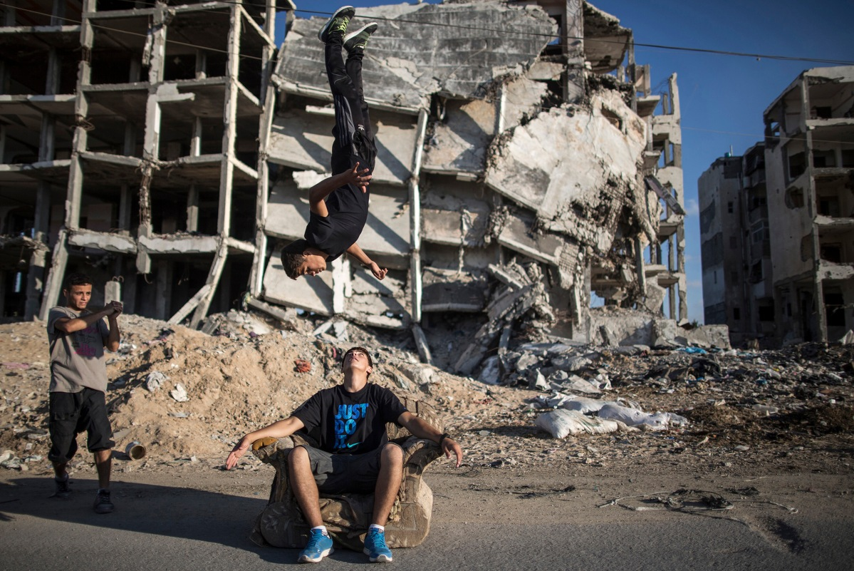 Young men practice parkour among the ruins of buildings that were damaged in the most recent conflict in Gaza, June 30 2015.