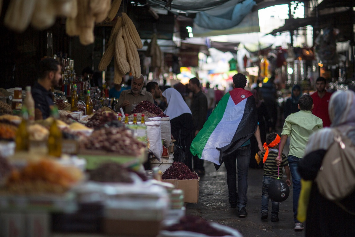 A palestinian man wearing a flag walks through the old central market in Gaza July 14, 2015.
