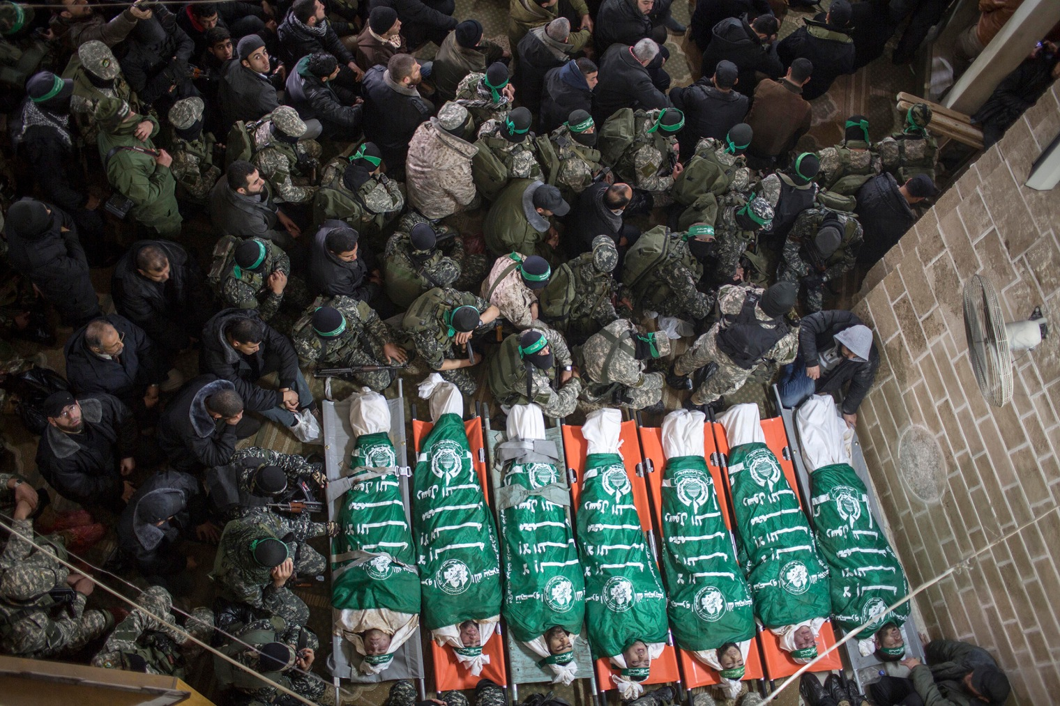 Palestinian fighters of the Izz Al-Din al-Qassam brigades, the military wing of Palestinian Hamas organization, sit around the bodies of seven fighters in Al Omari mosque during their funeral in Gaza City on January 29, 2016. Seven fighters from were killed after a tunnel built in the conflict with Israel collapsed.