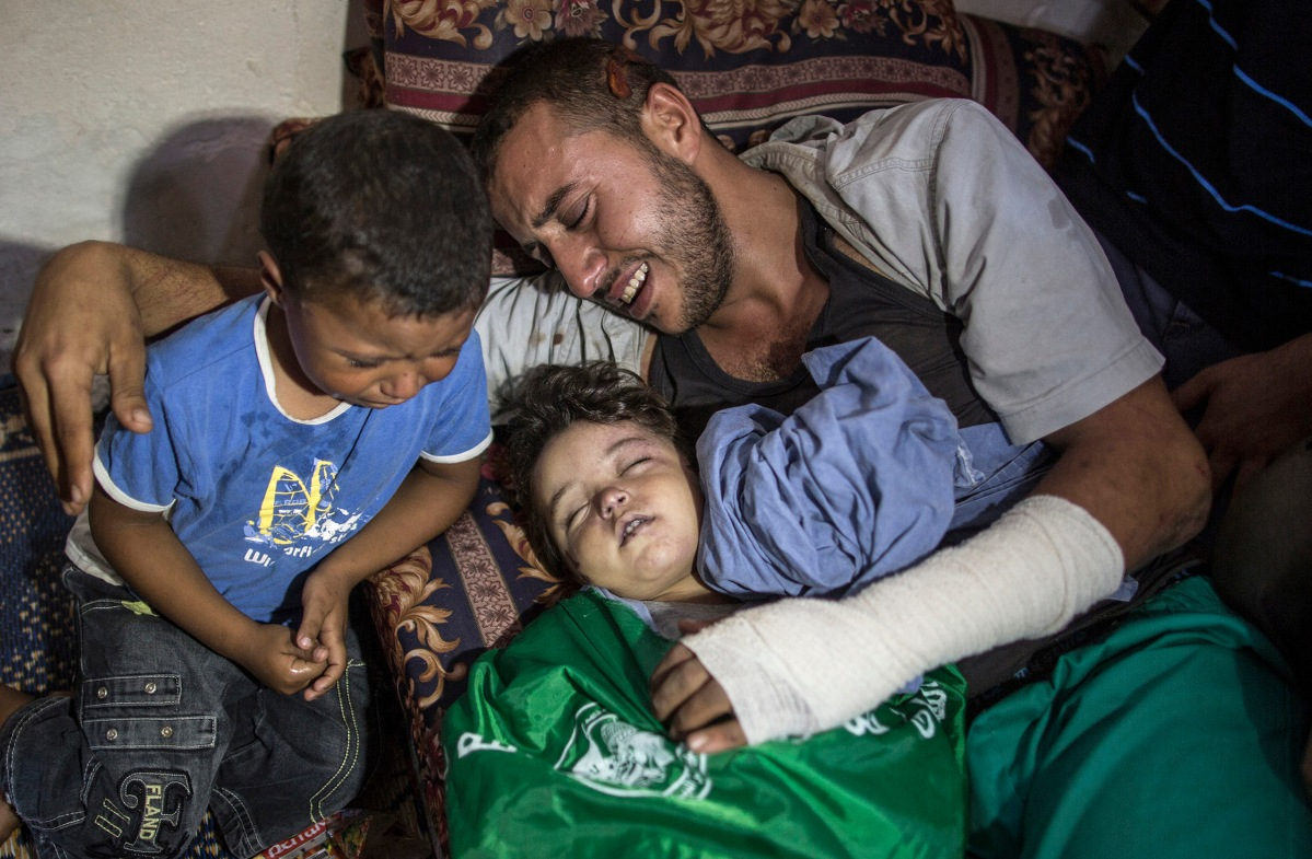 Palestinian father Yehiya Hassan and his son cry over the body of their two years old daughter and sisiter Rahaf Hassan during her funeral in the central Gaza Strip on October 11, 2015. An Israeli airstrike in the northern Gaza Strip killed a Palestinian woman who was five-months pregnant and her 2-year-old daughter. Four other members of the woman's family were injured when their home collapsed in Gaza City's Zaytoon neighbourhood, Gaza Health Ministry spokesman Ashraf al-Qedra said. The Israeli military said it targeted two weapons workshops after Palestinian militants launched a missile at the southern Israeli coastal city of Ashkelon, which was intercepted by the Iron Dome defence system.