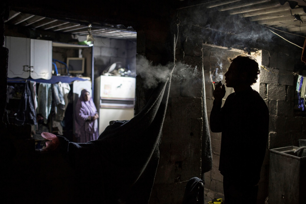 Ahmed Zayara 39, smokes inside his house during cold weather in an impoverished area in Al-Zitun neighborhood in the east of Gaza City, February 4, 2016.