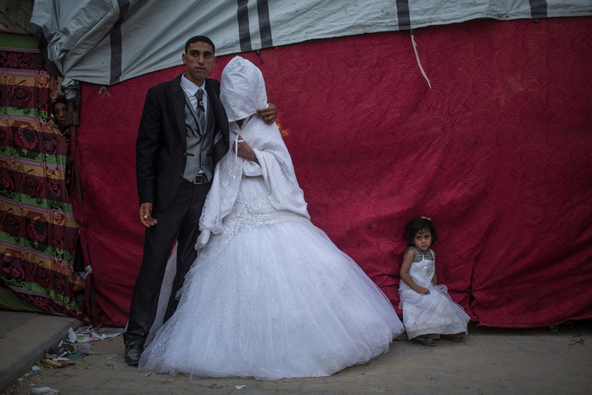 Palestinian groom Mohammed Yousef Al-Masri, 23, and his bride Zekriat Hamza Al-Masri, 20, pose for a picture next to their makeshift tent housing near their destroyed houses, which were damaged during the Israeli war against Gaza in the summer of 2014, during their wedding in Beit Hanun town in the northern Gaza Strip, October 1, 2015.