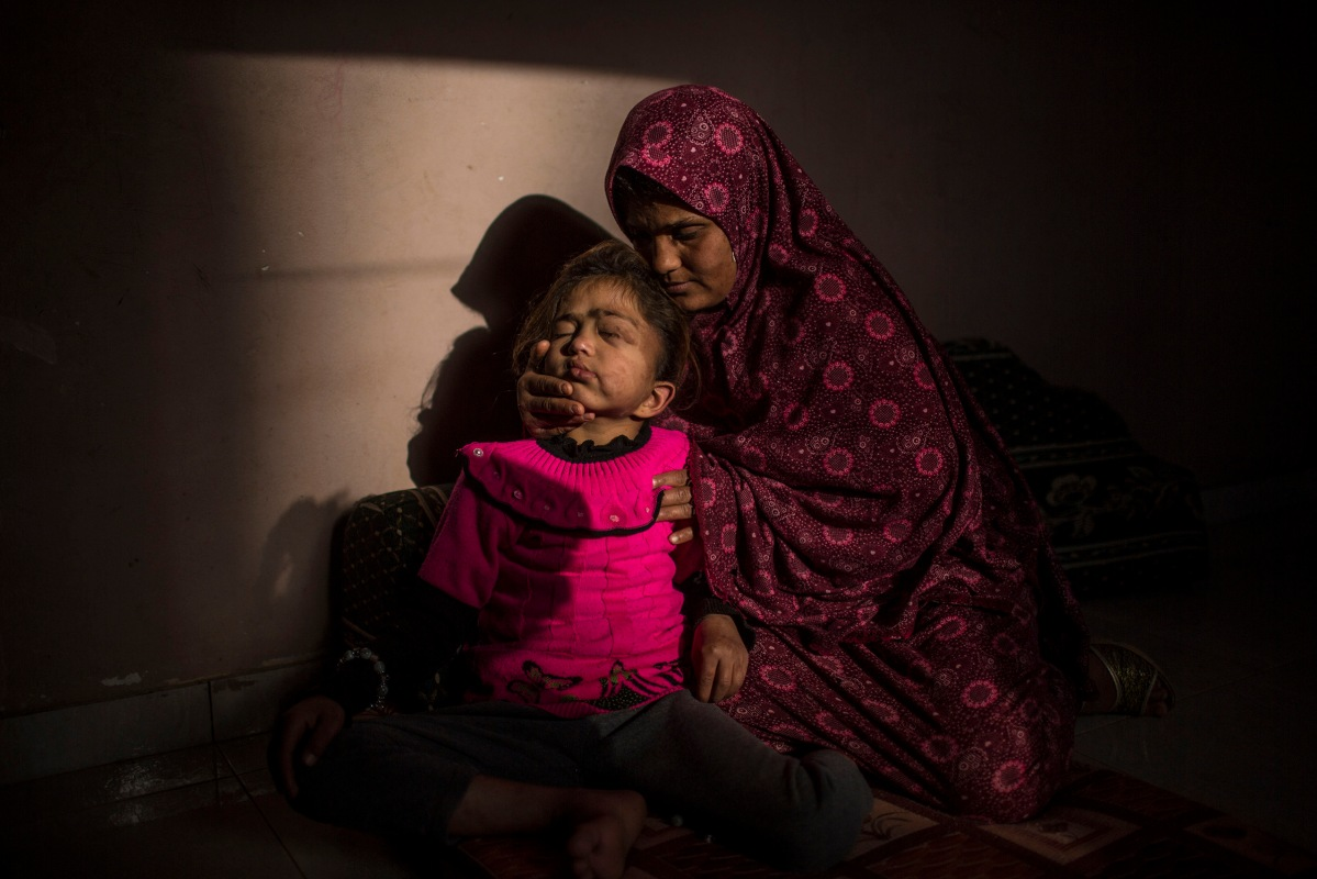 Samah, while hugging her 8-year old Daughter Enshirah, who is suffering from Brain Cancer and living in very bad economic circumstances. Samah hopes that Enshirah recovers and become able to go to school. Beit Hanoun, Gaza Strip.