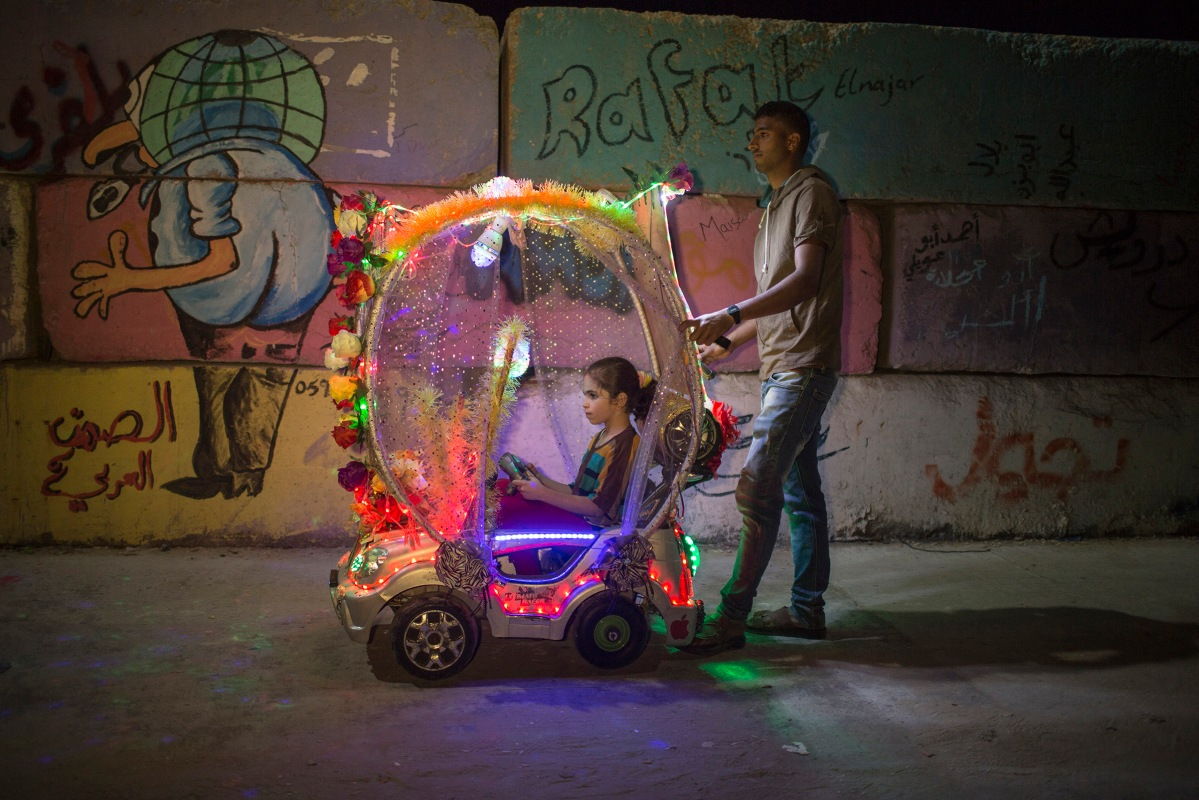 A Palestinian child riding in a colourful electric cart in Gaza port on June 1, 2015.