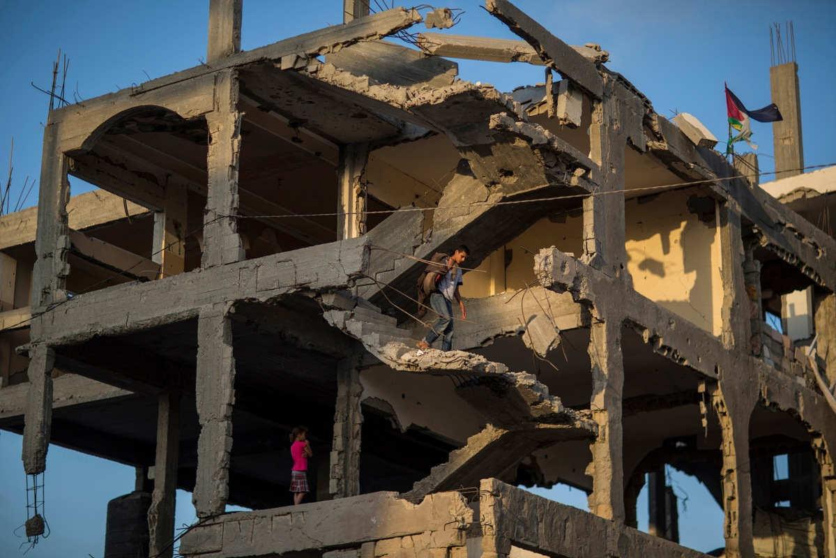 Ahmed Atawna going down at the stairs of their demolished house in Al-Shaaf area. The family live in a tent near the damaged house. in the east of Gaza on, 01 July 2015. By Wissam Nassar.