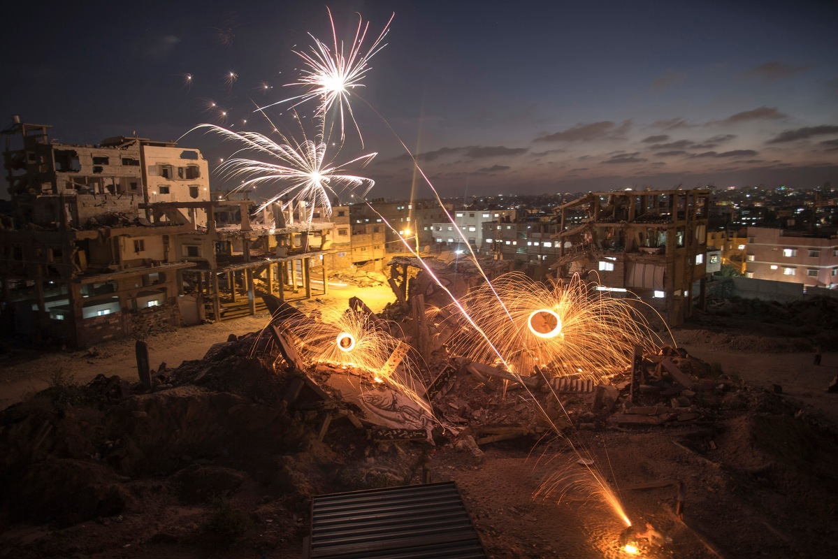 Palestinian young men set fireworks amid the rubble of destroyed houses in Al Shaaf neighborhood, in the east of Gaza City, Gaza Strip, July4, 2015. A group of Palestinians put their aims to light the darkness with fireworks at devastated urban areas in the Gaza Strip during the holy month of Ramadan. They were celebrating the graduation of public secondary students.By Wissam Nassar.