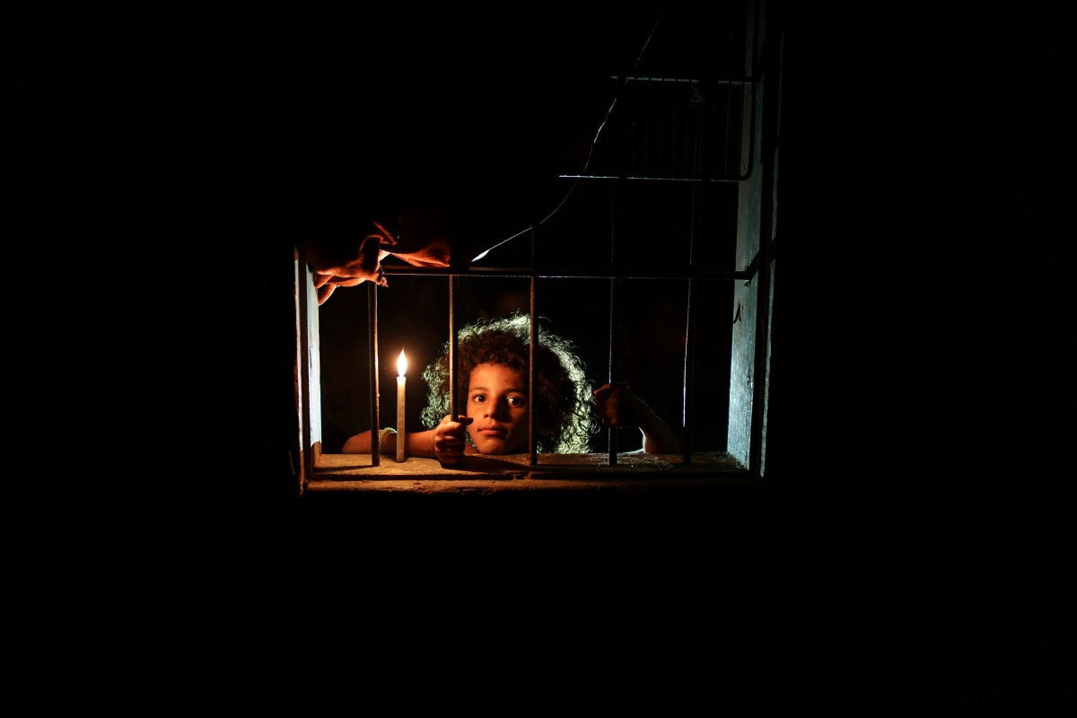 Sara Abushawish, aged 9, is looking through the window of her family courrugated iron sheet house beside candlelight in al-Zaitoun Nieghborhood in eastern Gaza Strip.on Aug. 12, 2017. Most Palestinian in Gaza Strip use batteries, generators or candles to light their homes. Residents of Gaza, home to 1.8 million people, experience some 20 of electricity outage per day. According to reports, the Gaza Strip sole functioning power on 16 April 2017 ran out of fuel and stopped working. The Gaza Power Generating Compan. By Wissam Nassar.