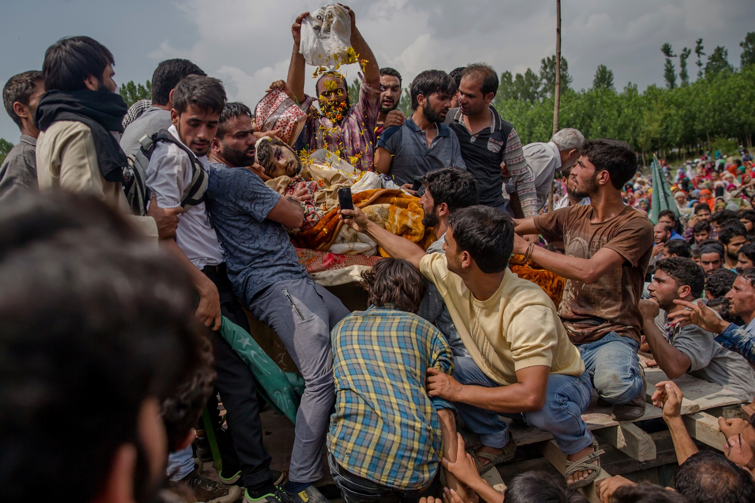 A villager showers flower petals over the body of senior militant Arif Nabi Dar as they display his body during his funeral in Lilhar, about 22 miles (35 km.) south of Srinagar on Aug. 1, 2017.