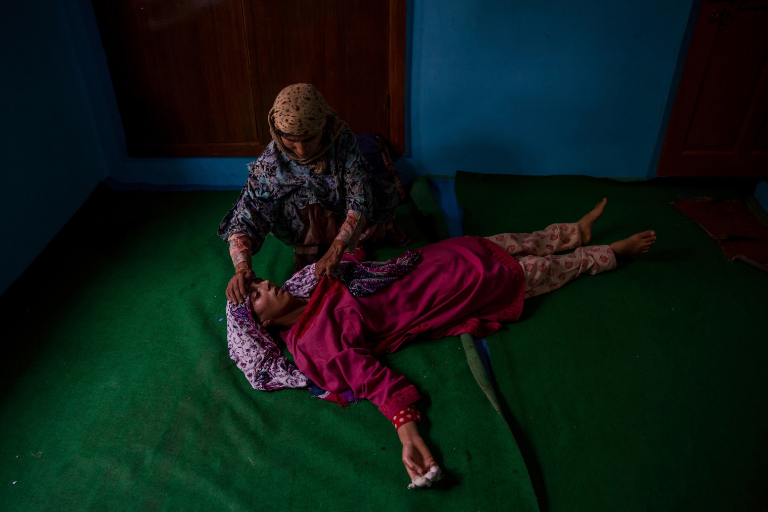 A woman tends to an unconscious relative of Kashmiri rebel Abid Hamid Mir during his funeral in Hajin, north of Srinagar, on Aug. 5, 2017.