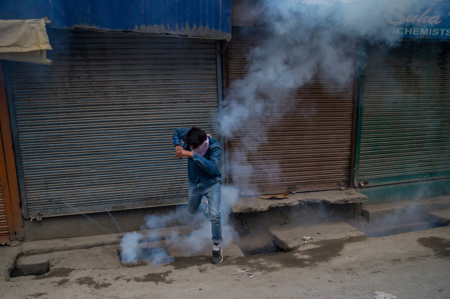 A masked Kashmiri protester jumps to avoid a tear gas shell fired by Indian policemen in Srinagar on May 26, 2017.